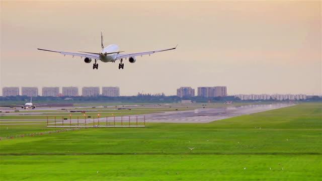 Airplane landing on runway at sunset