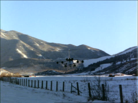 Airplane landing on runway in snow / mountains in background