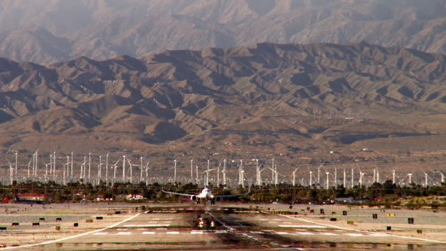 ws airplane landing on runway with wind turbine farm in background / palm springs, california, usa - palm springs california stock videos & royalty-free footage