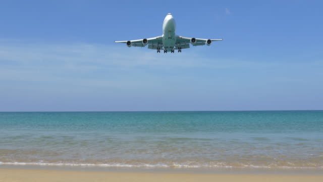 airplane landing over the beach. - boeing 747 stock videos and b-roll footage