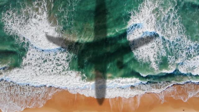 flugzeuglandung über dem meer, luftblick oben nach unten geschossen, schaumige meereswellen rollen und kommen auf einem sandstrand - bay of water stock-videos und b-roll-filmmaterial