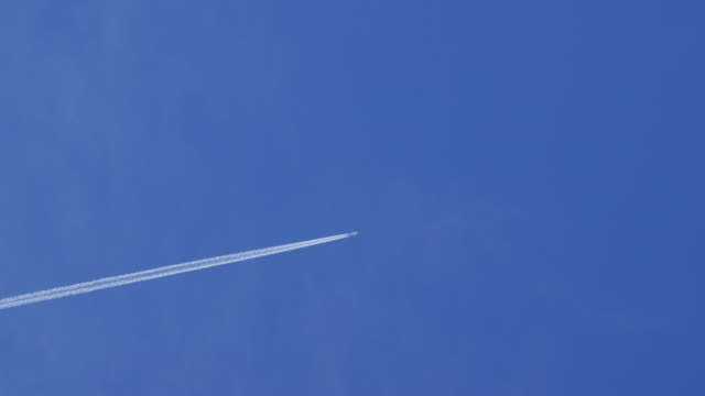 airplane leaves contrail in sky, wide shot - vapour trail stock videos & royalty-free footage