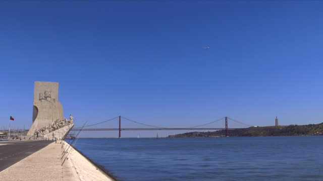 airplane over tejo, 25 de abril bridge and monument to the discoveries. - 4月25日橋点の映像素材/bロール