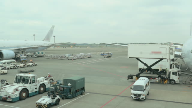 airplane parked at narita airport, narita, japan - fluggastbrücke stock-videos und b-roll-filmmaterial
