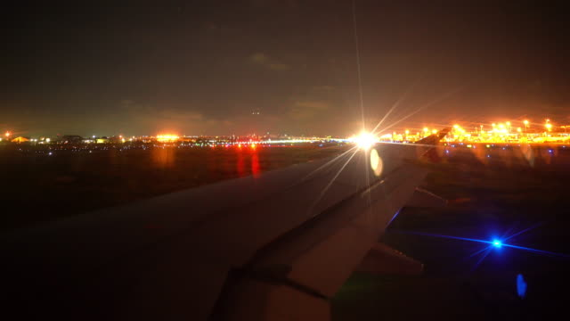 airplane passenger window with taking off with aircraft wing and flare light at night time - air traffic control tower stock videos & royalty-free footage