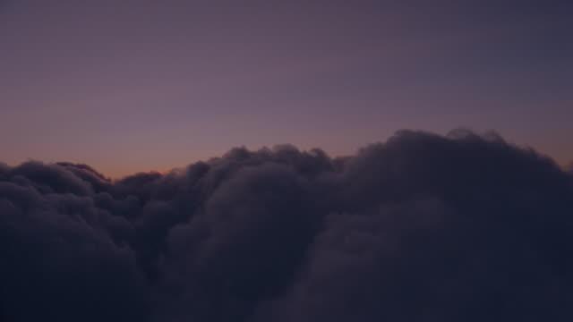 vídeos de stock, filmes e b-roll de airplane point of view above dark clouds at sunset / oxfordshire, england - céu romântico
