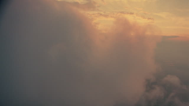 airplane point of view above white fluffy clouds at sunset / oxfordshire, england - 1分以上点の映像素材/bロール
