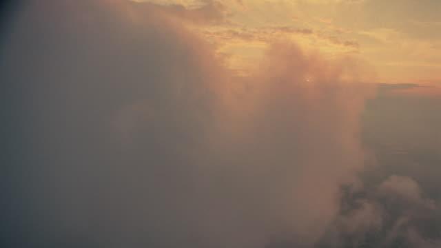 vídeos de stock e filmes b-roll de airplane point of view above white fluffy clouds at sunset / oxfordshire, england - 1 minuto ou mais