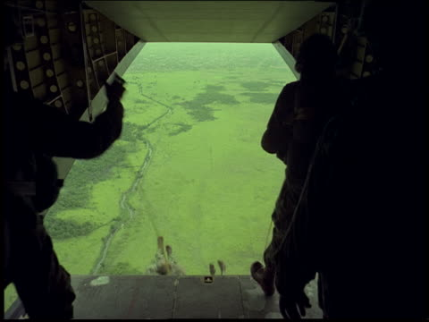 Airplane point of view Army soldiers parachuting out of plane into green countryside / Rio de Janeiro, Brazil