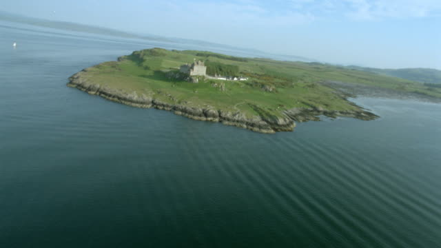 vídeos de stock e filmes b-roll de aerial airplane point of view fast over water to duart castle on coastline / isle of mull, scotland - ilha mull