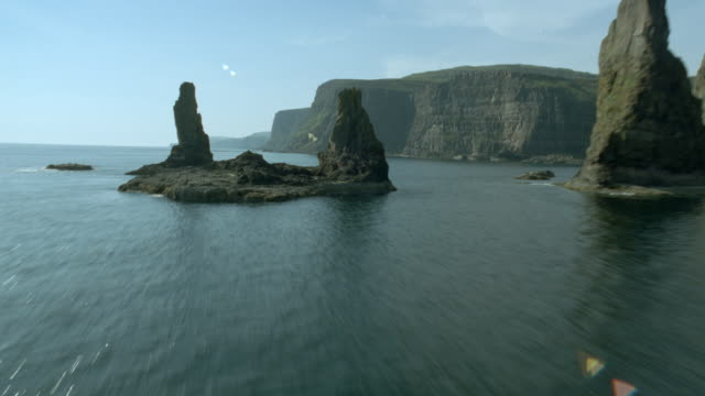 AERIAL airplane point of view ocean, rock formations + cliffs / Macleod's Maidens, Isle of Skye, Scotland