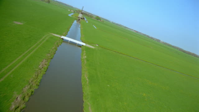 aerial airplane point of view over green fields, canal + windmill / alkmaar, northwestern holland - dutch culture stock videos & royalty-free footage