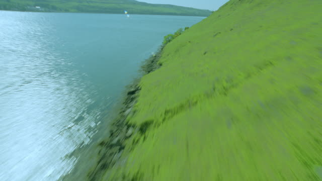 aerial airplane point of view over green hills by lake / loch harport, isle of skye, scotland - loch点の映像素材/bロール