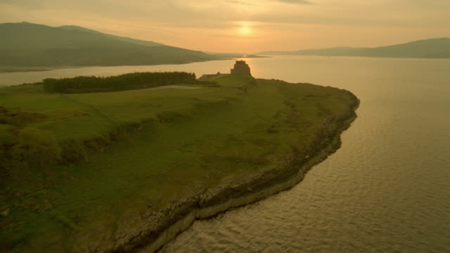 aerial airplane point of view past duart castle on coastline at sunset / isle of mull, scotland - mull stock-videos und b-roll-filmmaterial