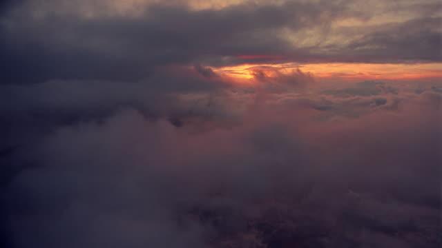 vídeos de stock, filmes e b-roll de airplane point of view through clouds at sunset / oxfordshire, england - céu romântico