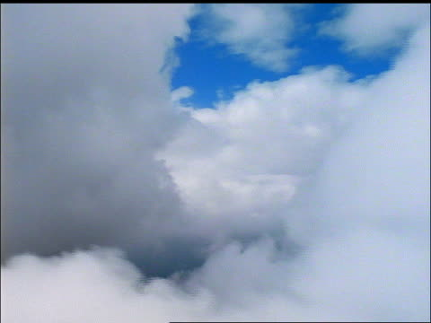 Airplane point of view thru white fluffy clouds / County Limerick, Ireland