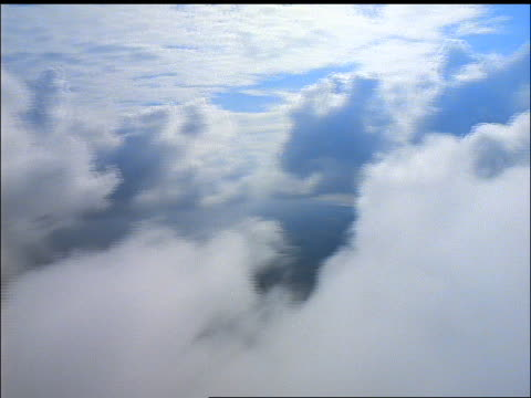 Airplane point of view thru white fluffy clouds over land / County Cork, Ireland