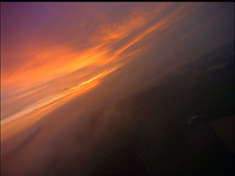 Airplane point of view thru wispy clouds with land below at twilight / County Waterford, Ireland