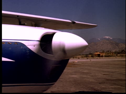 1965 film montage cu airplane propeller starting up/ ws plane taking off  as man on runway waves goodbye/ yucca valley, california - propeller stock videos & royalty-free footage