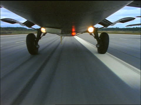 Airplane rear point of view speeding on runway + taking off / landing gear retracts / Swedish Air Force jet