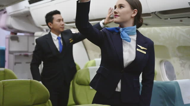 airplane stewardess flight attendant closes baggage compartments. - crew stock videos & royalty-free footage