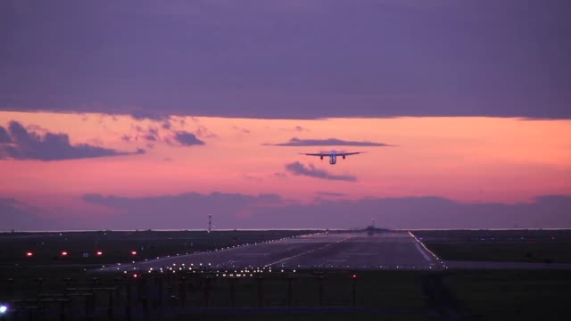 Airplane taking off at dawn with purple sky