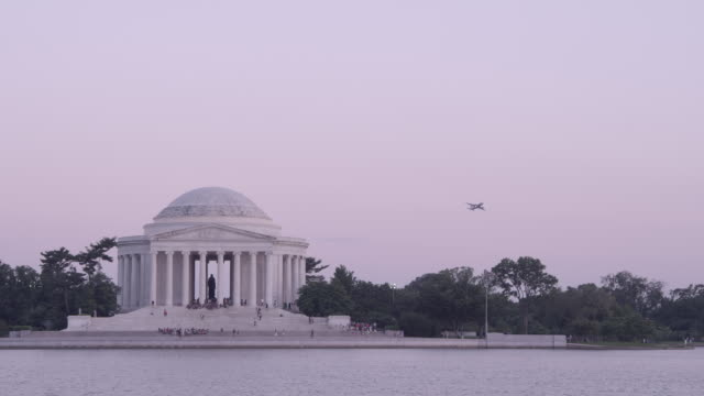 ws airplane taking off behind jefferson memorial at dusk / washington dc, united states - トーマス ジェファーソン点の映像素材/bロール