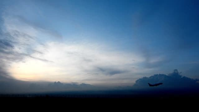 airplane taking off from airport at sunset - partire video stock e b–roll