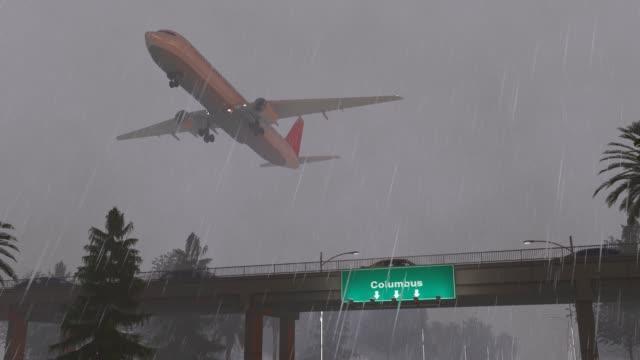 vidéos et rushes de avion qui décolle de columbus airport états-unis jour de pluie - panneau de rue