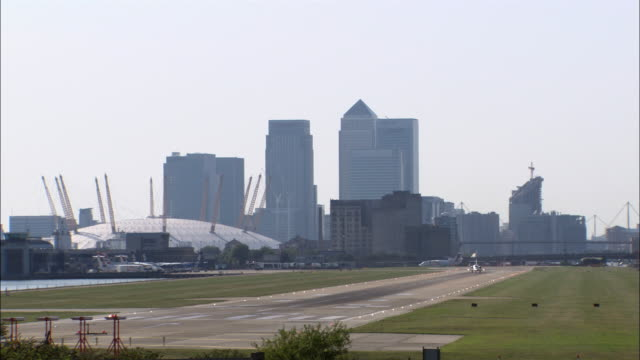 airplane taking off from london city airport with millennium dome and canary wharf in background / london, england - dome stock videos & royalty-free footage