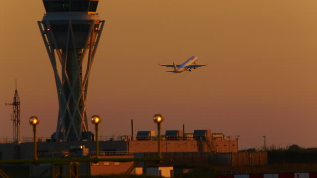vídeos de stock, filmes e b-roll de airplane taking off in the barcelona airport on sunset light with communication tower taken with telephoto lens. - torre de controle de tráfego aéreo