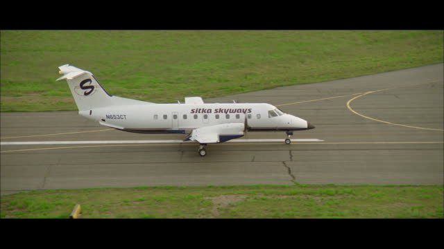 pan airplane taxiing down the runway - campo d'aviazione video stock e b–roll