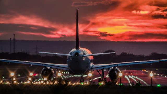 vidéos et rushes de avion taxiing sur la piste au coucher du soleil - aérodrome