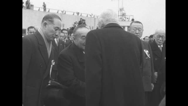 airplane taxiing on tokyo airfield / canadian and japanese flags flying in breeze / canadian prime minister louis st laurent deplaning / line of... - sideburn stock videos and b-roll footage
