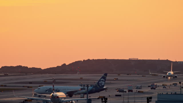 ls airplane towed by tug vehicle to runway against orange sunset sky while two other aircraft taxi to and from runway - air traffic control tower stock videos & royalty-free footage