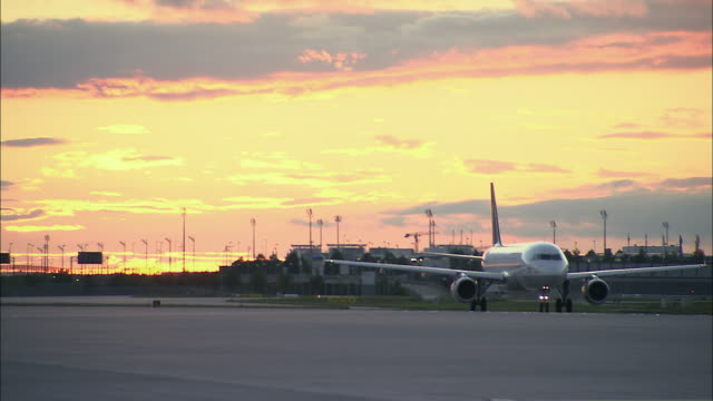 stockvideo's en b-roll-footage met ws airplane traveling on airport runway at sunset / munich, germany - münchen vliegveld