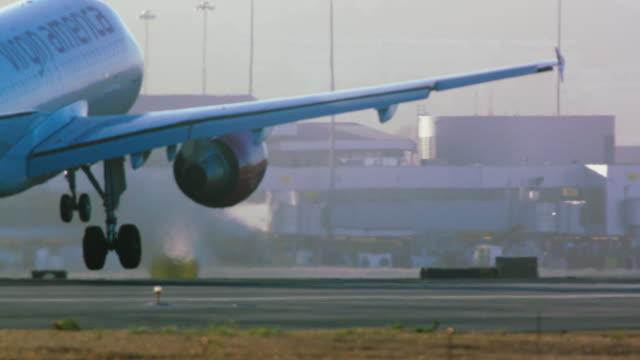 airplane wheels touch down on runway as virgin america passenger jet lands - タッチダウン点の映像素材/bロール