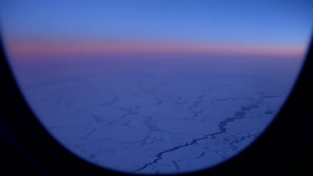 airplane window view of the arctic landscape at dusk - ice sheet stock videos and b-roll footage