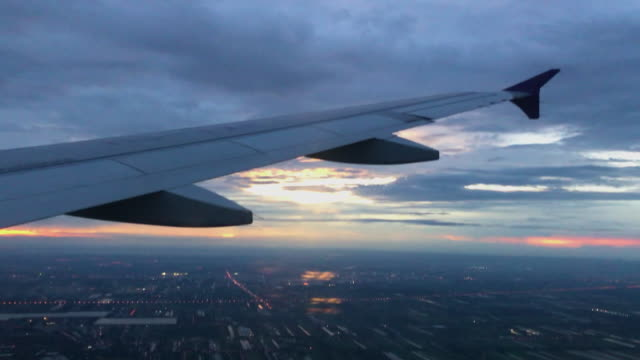 airplane wing flying with city view at sunset time at evening before landing on runway at airport - aircraft wing stock videos & royalty-free footage