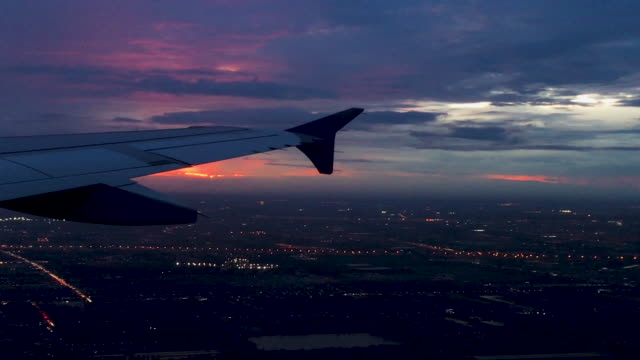 airplane wing flying with city view at sunset time at evening before landing on runway at airport - runway stock videos & royalty-free footage