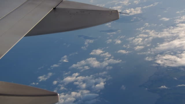 airplane wing in front of clouds and ocean - airplane part stock videos and b-roll footage
