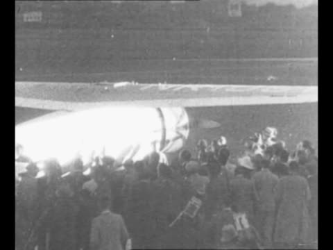 vídeos de stock e filmes b-roll de airplane winnie mae takes off flying away as it continues its roundtheworld flight / crowds surround the plane in berlin after its night landing at... - 1931