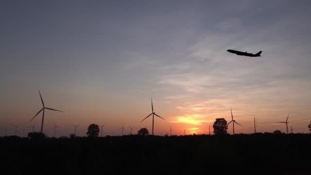 vidéos et rushes de avion avec l'turbine d'énergie éolienne au coucher du soleil. - développement durable