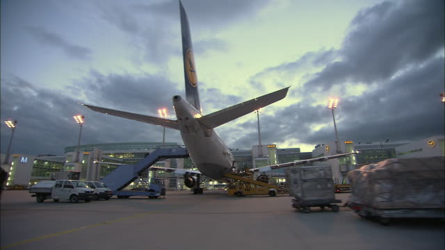 stockvideo's en b-roll-footage met la ws airplanes and bus on airport runway at dusk / munich, germany - münchen vliegveld