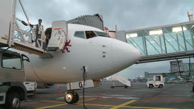 cu airplanes at airport / airport luxembourg-findel, luxembourg - fluggastbrücke stock-videos und b-roll-filmmaterial