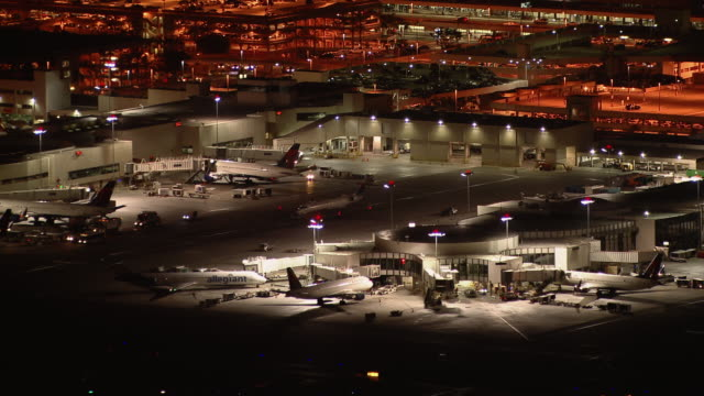 stockvideo's en b-roll-footage met airplanes at gates at the terminals of los angeles international airport, at night. - lax airport