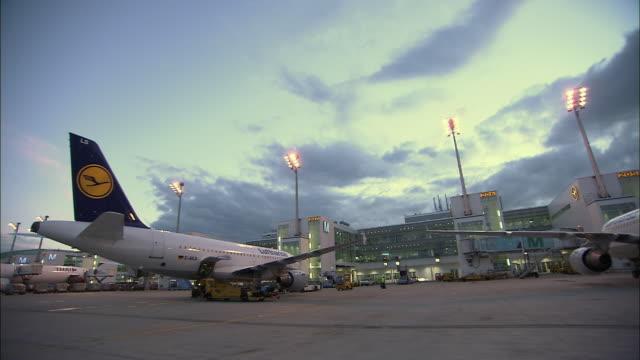 stockvideo's en b-roll-footage met la ws airplanes on airport runway at dusk / munich, germany - münchen vliegveld