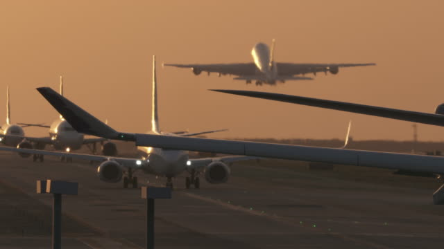 airplanes taxi at sunset - airbus stock-videos und b-roll-filmmaterial