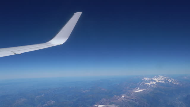 Airplane's wing flying over Alps