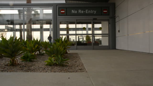 stockvideo's en b-roll-footage met airport courtyard looking at a sign no reentry over a door to the airport corridor with people walking by inside long beach california - long beach californië